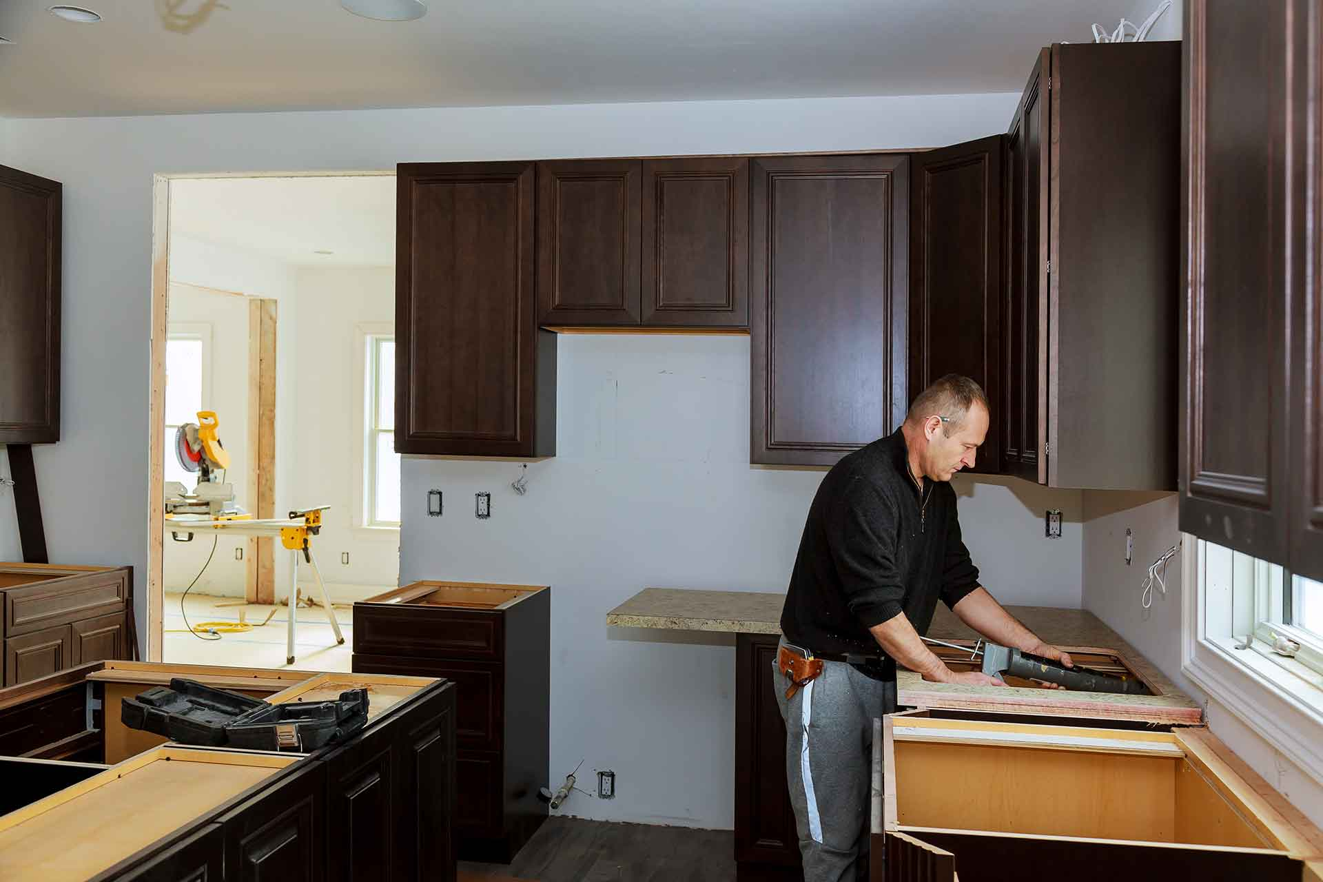 How much do custom kitchen cabinets cost - contractor installing kitchen cabinets